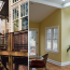 A diptych showing exterior deck stairs and interior of sunroom with skylights, yellow walls, and hardwood floors.