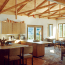 A kitchen and dining area with vaulted ceiling, exposed beams, and lots of natural light.