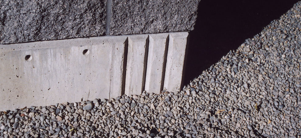 A close-up of the corner of a well-designed concrete foundation with a dark masonry block wall on top.