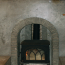 A closeup of a custom concrete fireplace with a woodstove in it.