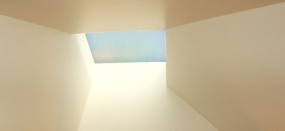 Looking up at a blu sky through an angular skylight well.